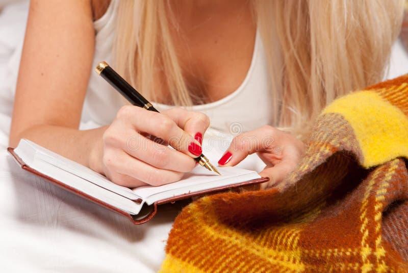 детеныши сочинительства женщины th дневника лежа стоковые фото