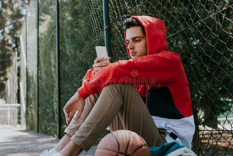 Детеныши с мобильным телефоном на баскетболе стоковое изображение