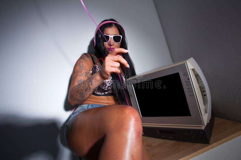 Детеныши тяжело татуировали женщину смотря винтажное телевидение стоковая фотография rf