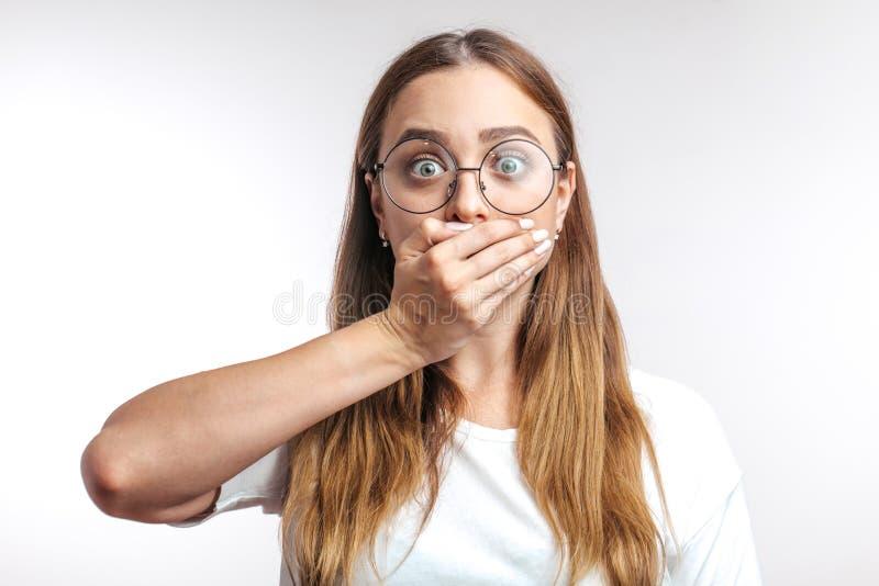 Детеныши удивили кавказскую женщину закрывая ее рот с рукой на белой предпосылке стоковые изображения rf