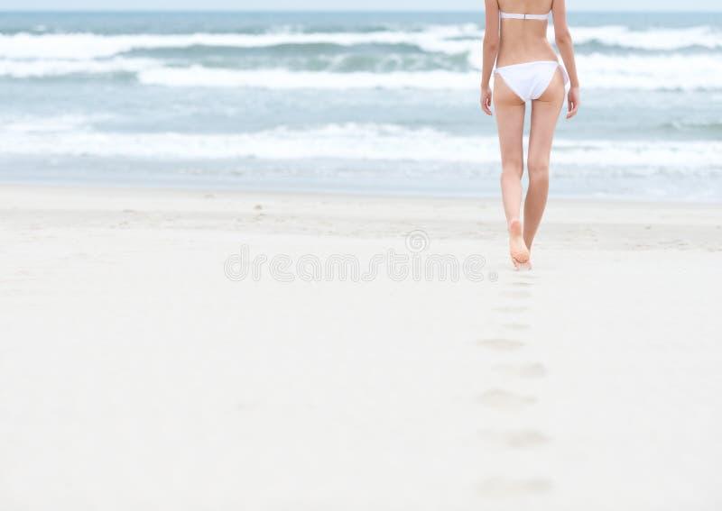 Тонкая девушка в белом swimsuit гуляя к океану. стоковые фотографии rf