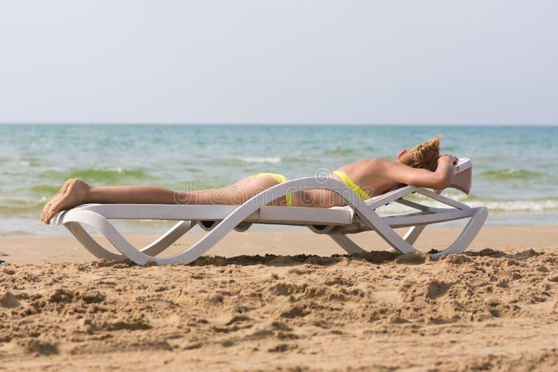 Детеныши уменьшают загоренный пляж моря женщины лежа на стороне deckchair вниз стоковая фотография