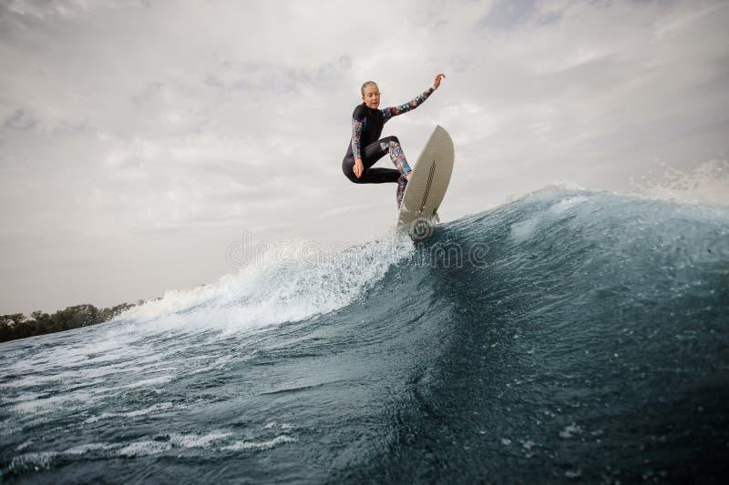 Детеныши уменьшают и активная женщина в купальнике скача вверх по голубому aga волны стоковое изображение