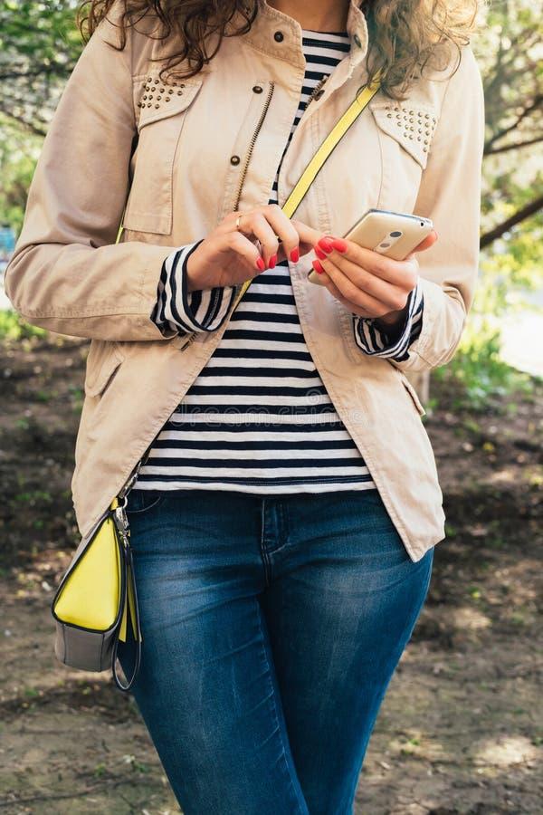 Детеныши уменьшают положение женщины и использовать мобильный телефон outdoors Весна стоковое изображение