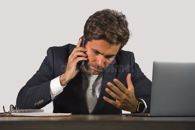 детеныши усилили и бизнесмен осадки работая на говорить стола компьютера офиса расстроенный на мобильном телефоне чувствуя утомля стоковая фотография rf