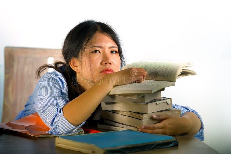Детеныши усилили и расстроили азиатского китайского студента подростка работая крепко полагаться на куче блокнотов и книг на сокр стоковое фото rf