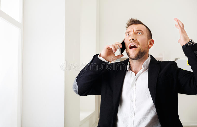 Детеныши усилили мобильный телефон звонка бизнесмена в современном офисе стоковое фото
