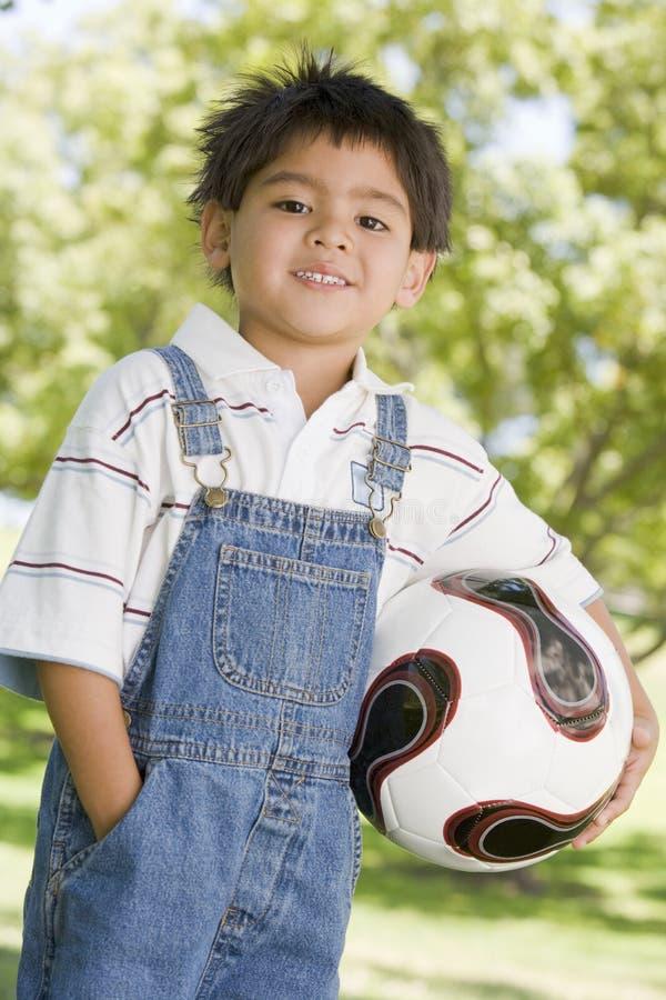 детеныши футбола удерживания мальчика шарика outdoors ся стоковое изображение