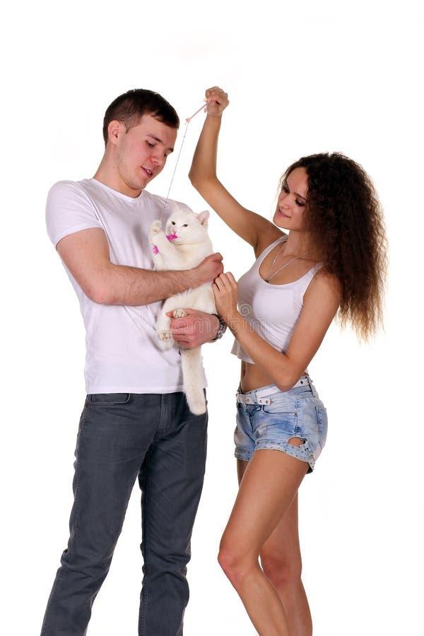 Детеныши экономно расходуют и кот владением жены изолированный на белой предпосылке стоковое фото