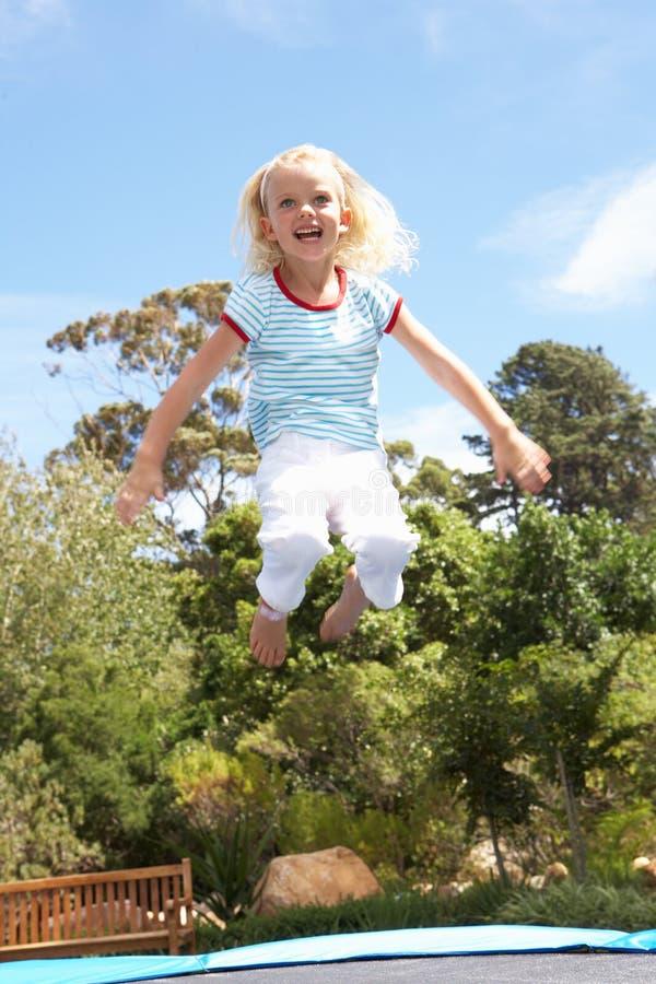 детеныши trampoline девушки сада скача стоковое фото