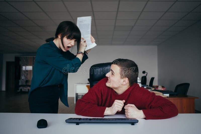 Детеныш и очень злая бизнес-леди выкрикивая на ее коллеге и хотят ударить свои безопасности стоковые изображения rf