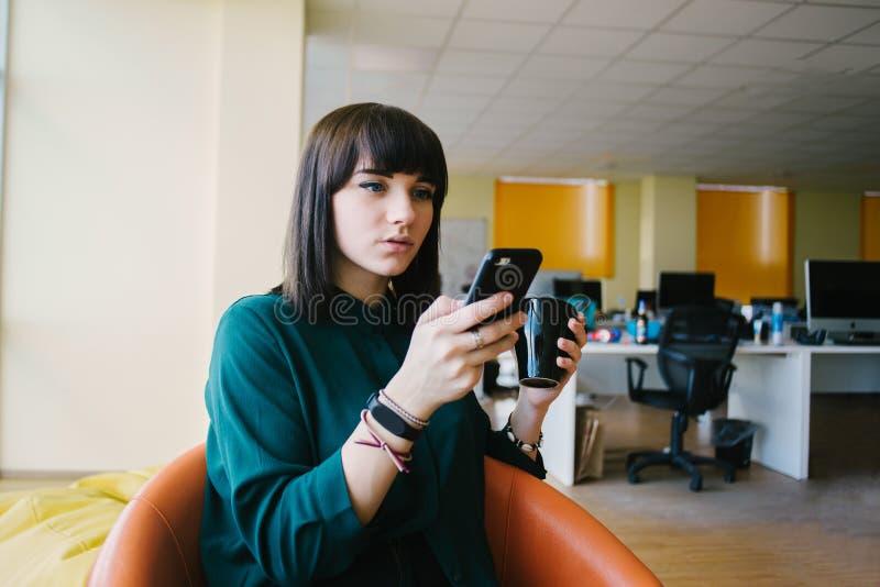 Детеныш и очень красивая бизнес-леди используют телефон и держать чашку кофе На фоне работ офиса стоковые фото