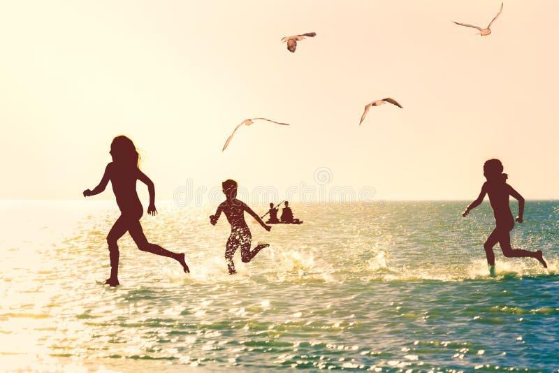 Дети бежать вдоль моря на заходе солнца стоковая фотография rf
