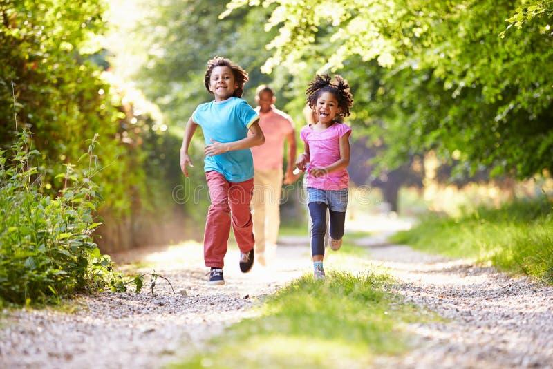 Дети бежать в сельской местности с отцом стоковая фотография rf