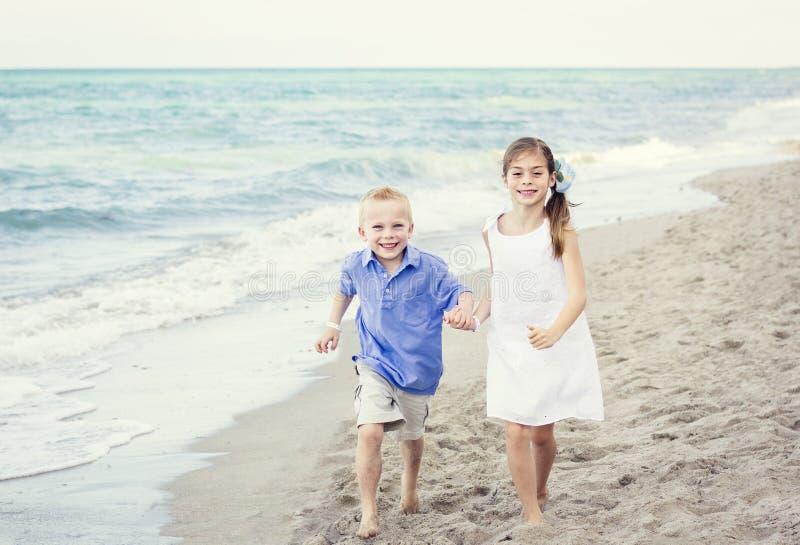 Дети бежать совместно вдоль пляжа стоковые изображения rf