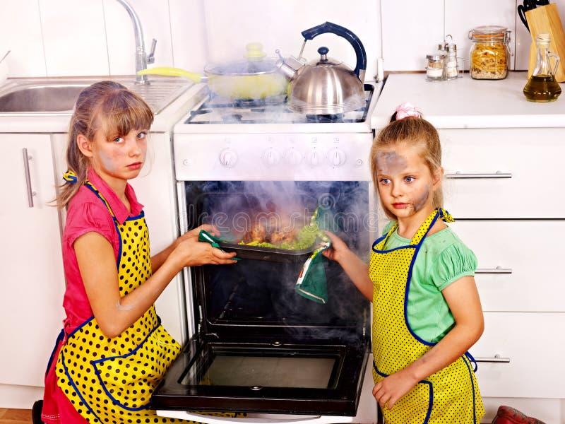 Дети варя цыпленка на кухне стоковая фотография