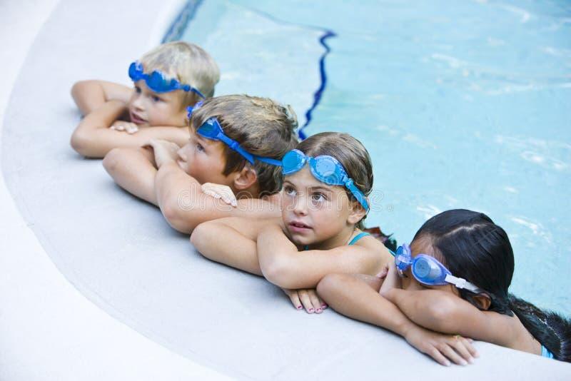 дети вися бассеин отдыхая бортовое заплывание стоковое изображение rf