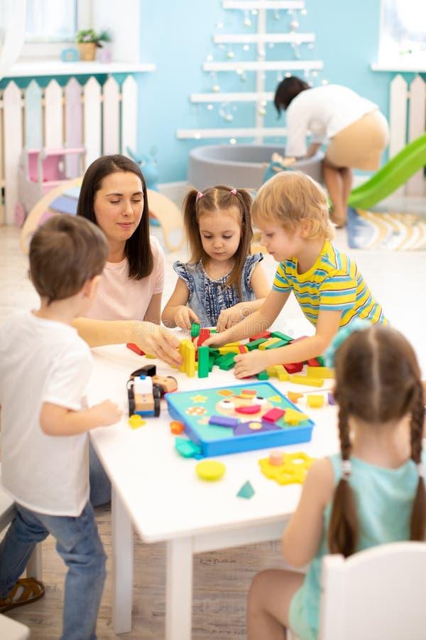 Дети воспитателя помогая играя с конструктором блока в daycare стоковые изображения rf