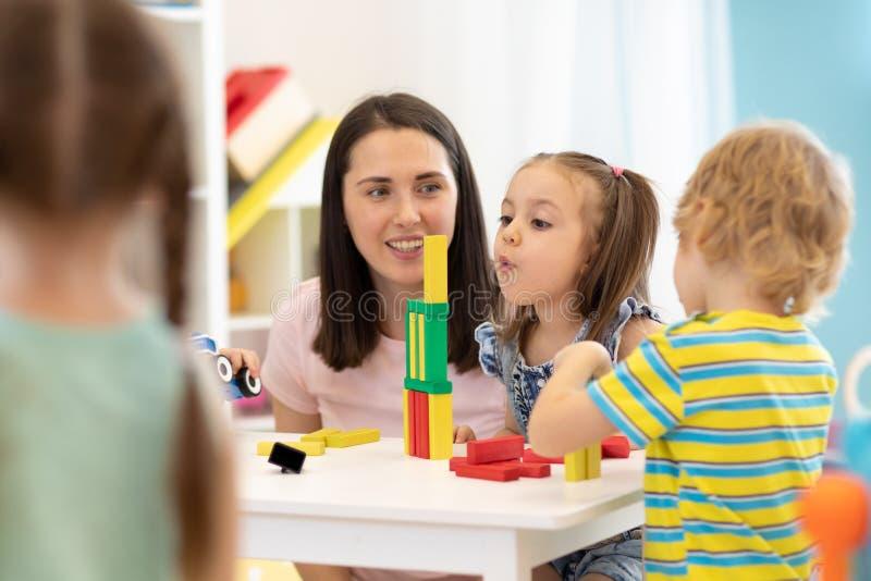 Дети воспитателя помогая играя с конструктором в детском саде стоковое изображение
