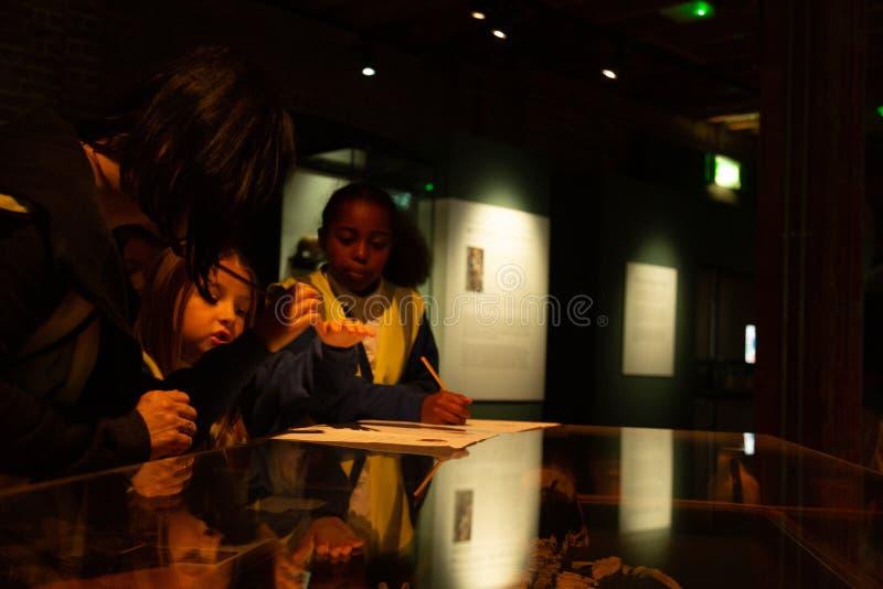 Дети во время посещения на римской мертвой выставке на музее районов доков Лондона стоковые изображения rf