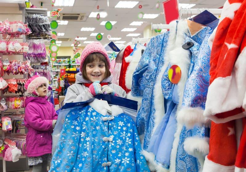 Дети выбирая обмундирование ` s Eve Нового Года в магазине стоковое изображение rf