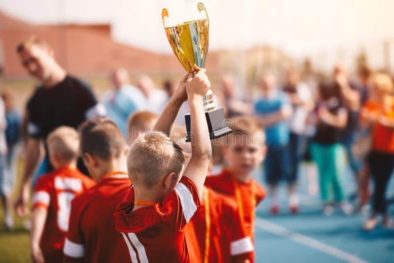 Дети выигрывая конкуренцию спорт Футбольная команда детей с трофеем Мальчики празднуя чемпионат футбола в начальной школе стоковое фото rf