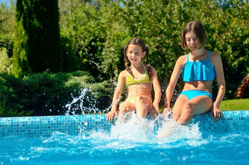 Дети в бассейне имеют потеху и брызгают в воде стоковая фотография rf