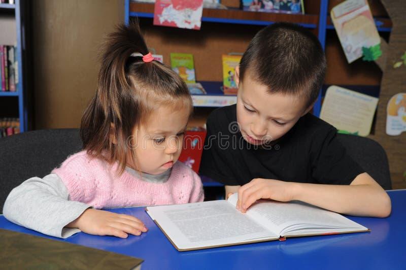 Дети в библиотеке читая интересную книгу Учить маленькой девочки и мальчика стоковое фото rf