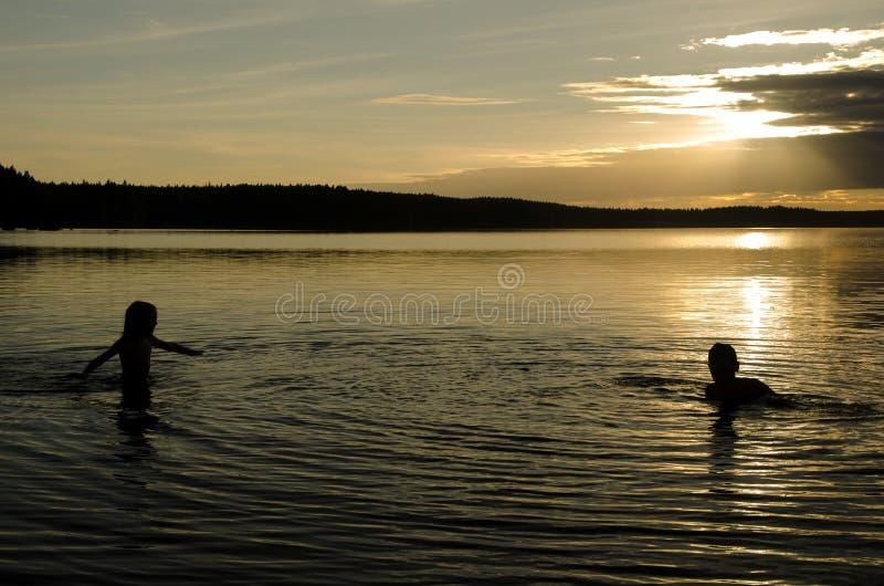Дети в воде озера на заходе солнца стоковые фотографии rf