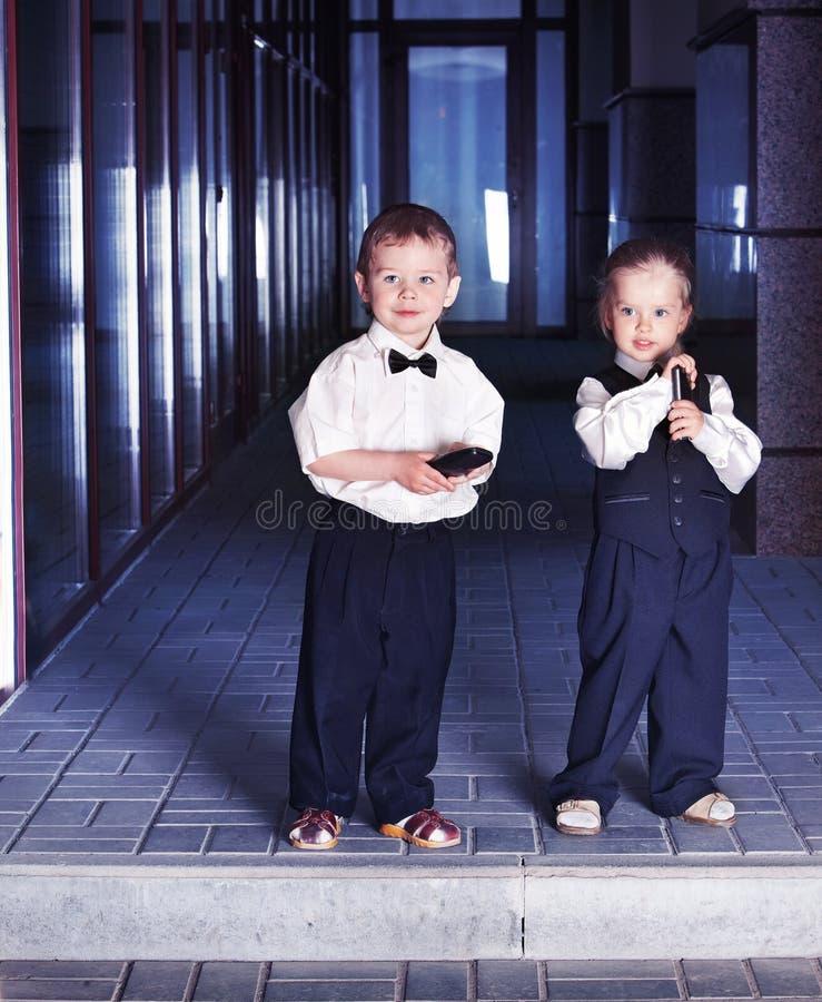 Дети в деловых костюмах принимают заем для образования стоковые фото