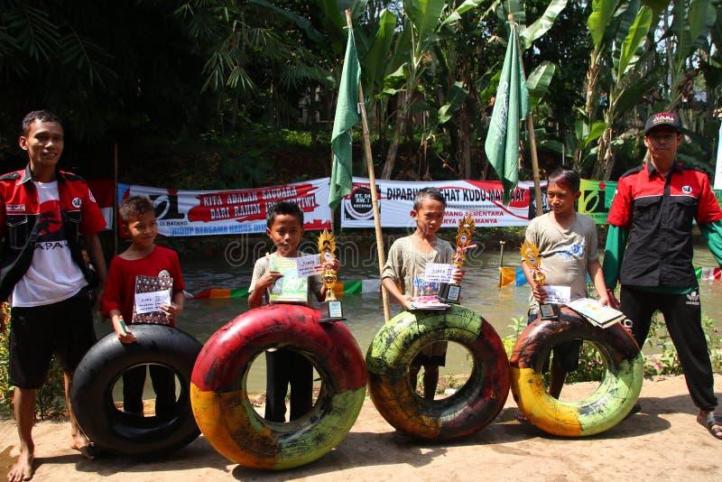 Дети в деревне играют жизнерадостные водные горки на реке, стоковое изображение rf