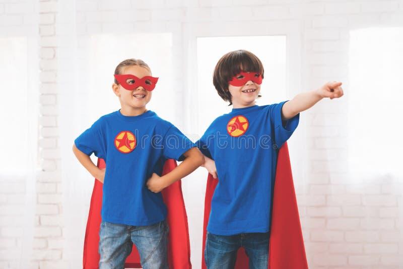 Дети в красных и голубых костюмах супергероев Они в масках Дети представляя в светлой комнате стоковое изображение rf