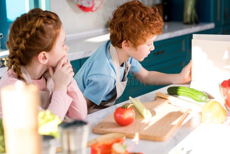 дети в рисбермах читая coobook пока подготавливающ салат овоща совместно стоковые фото