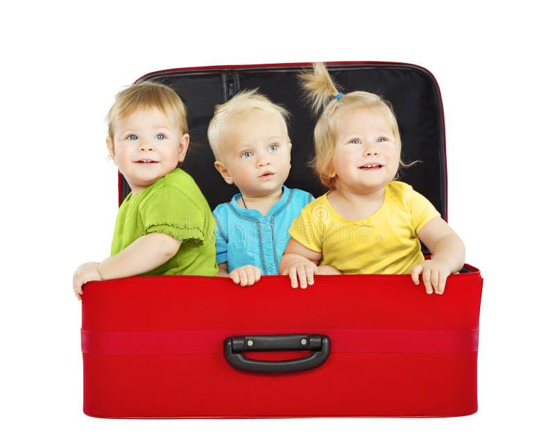 Дети в случае перемещения, 3 путешественника детей внутри чемодана стоковые изображения