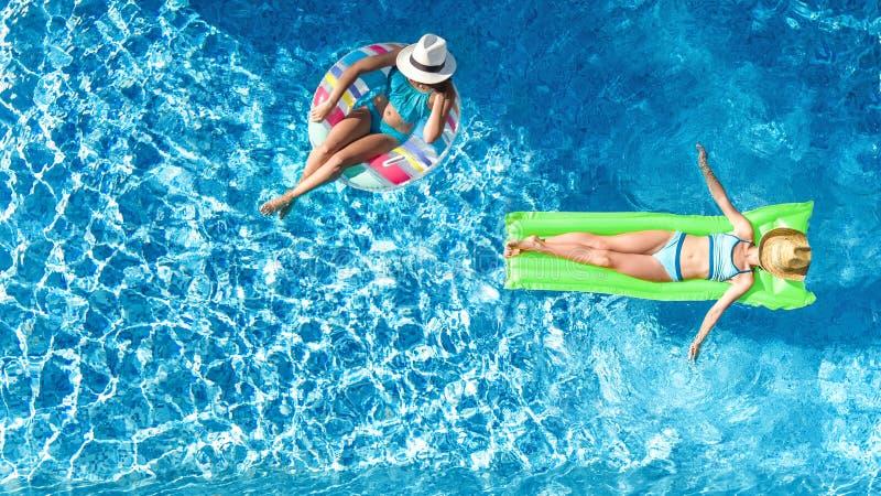 Дети в fom взгляда трутня бассейна воздушном выше, счастливые дети плавают на раздувном донуте кольца и тюфяк, девушки имеет поте стоковое изображение rf