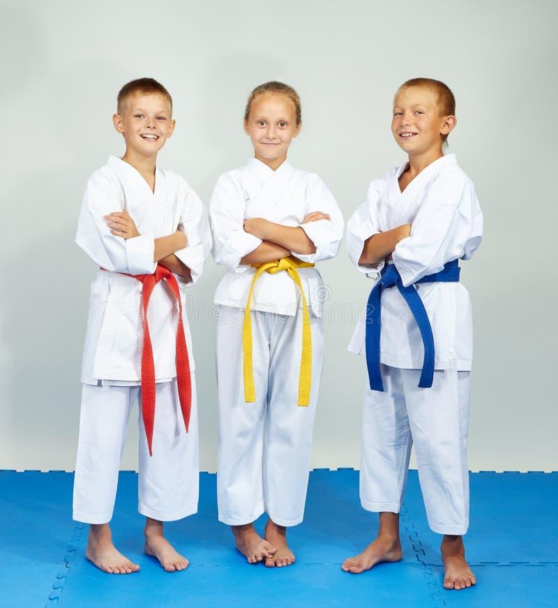 Дети в karategi стоят на голубые циновки стоковое изображение