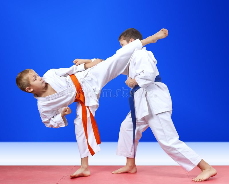 Дети в karategi тренируют руку пунша и дуют нога стоковое фото rf