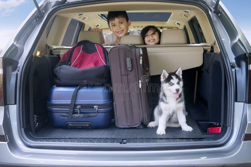 Дети готовые на праздник с собакой в автомобиле стоковое изображение