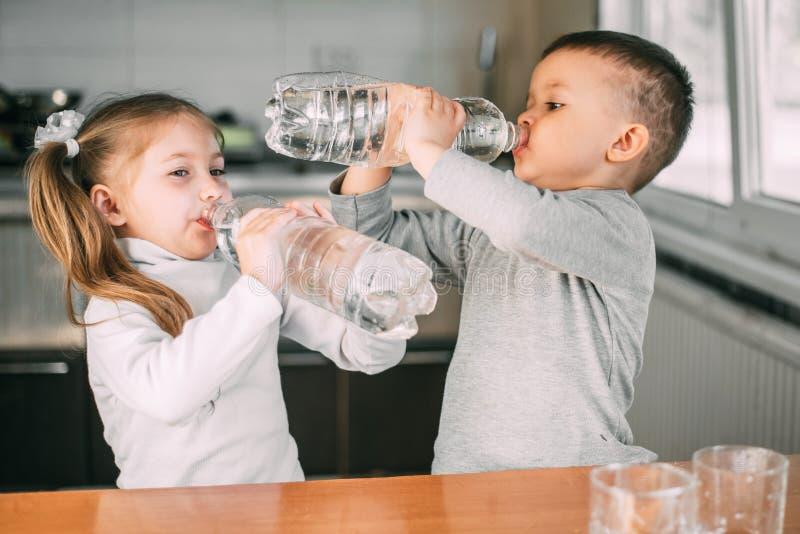 Дети-девочки и мальчики пьют воду из бутылок с литрами очень жадно, жажда стоковое фото