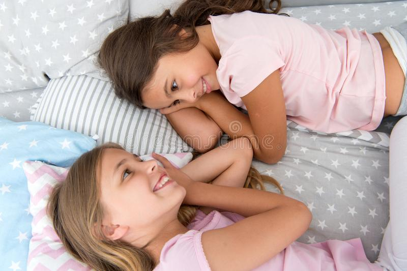 Дети девушек кладут на кровать с милым взгляд сверху подушек Концепция партии пижам девушки потехи имея Girlish секреты честные стоковое изображение