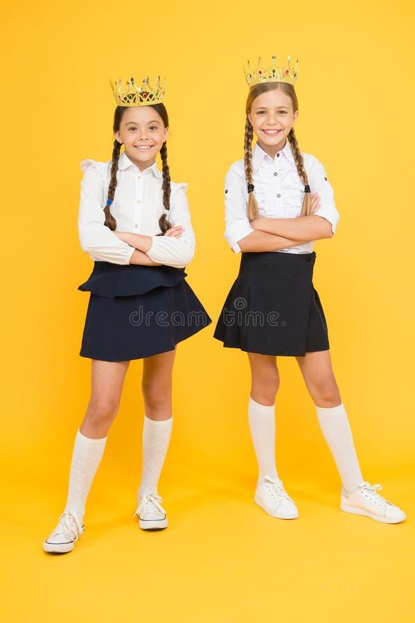 Дети девушек отображая роскошный образ жизни Коронование награды Гениальные зрачки Школьницы носят золотой символ крон  стоковые фотографии rf