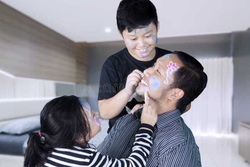Дети делая сторону крася к их отцу стоковая фотография rf