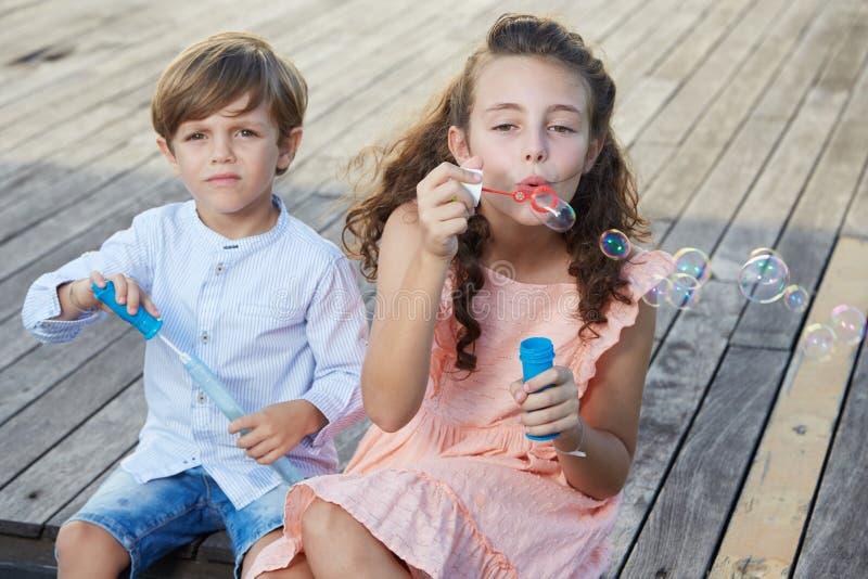 Дети дуя пузыри мыла стоковая фотография
