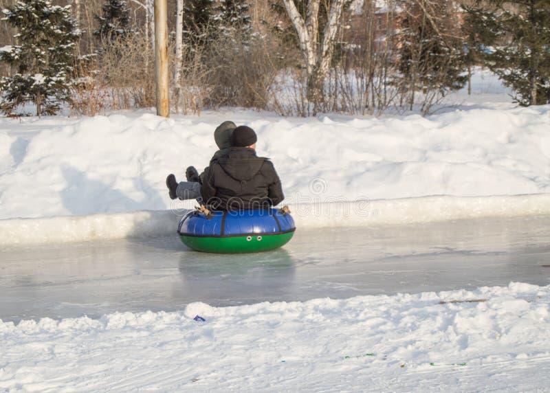 Дети едут со скольжениями льда на раздувном трубопроводе, на высокой скорости скольжении на скользком льде, развлечениях зимы и н стоковая фотография rf
