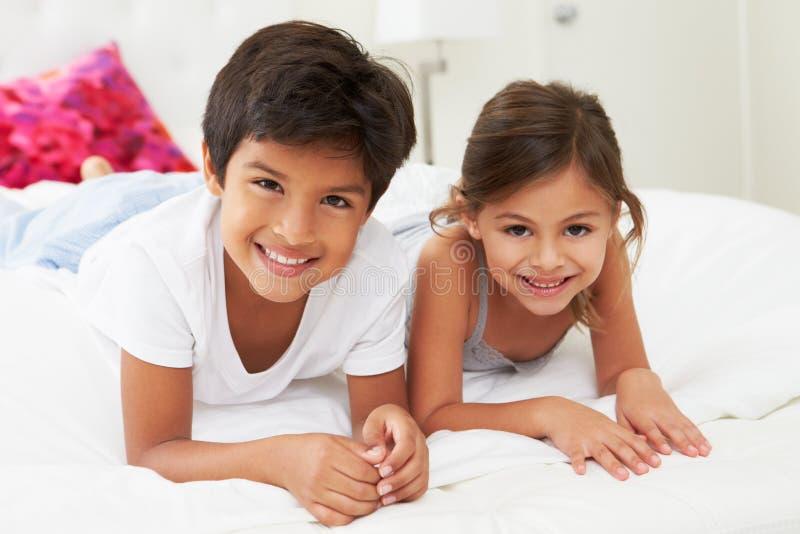 Дети лежа на кровати в пижамах совместно стоковая фотография rf