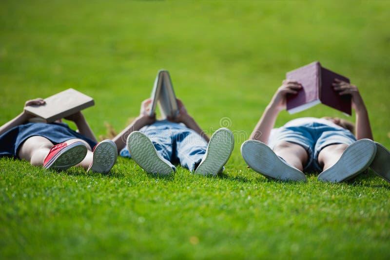 Дети лежа на траве совместно и книгах чтения стоковое изображение