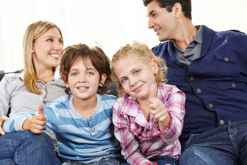 Дети держа большие пальцы руки вверх между родителями стоковое изображение rf