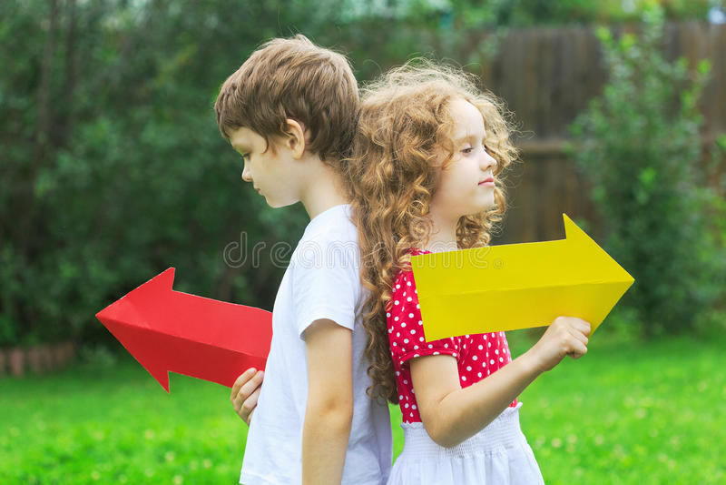 Дети держа стрелку цвета указывая справедливо и налево, в лето стоковая фотография rf