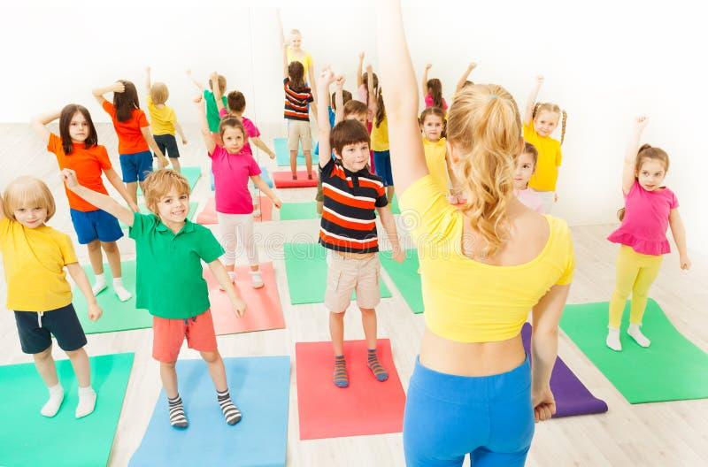 Дети делая гимнастические тренировки с женским тренером стоковое фото rf