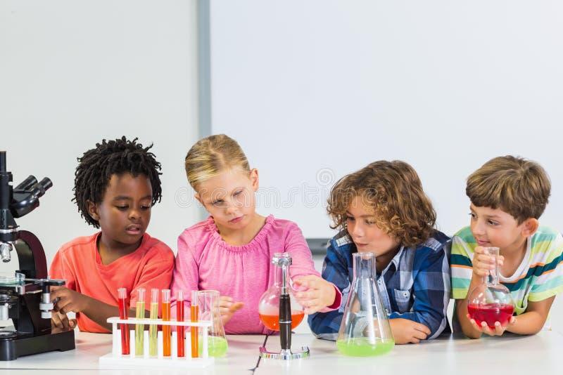 Дети делая химический эксперимент в лаборатории стоковые фотографии rf